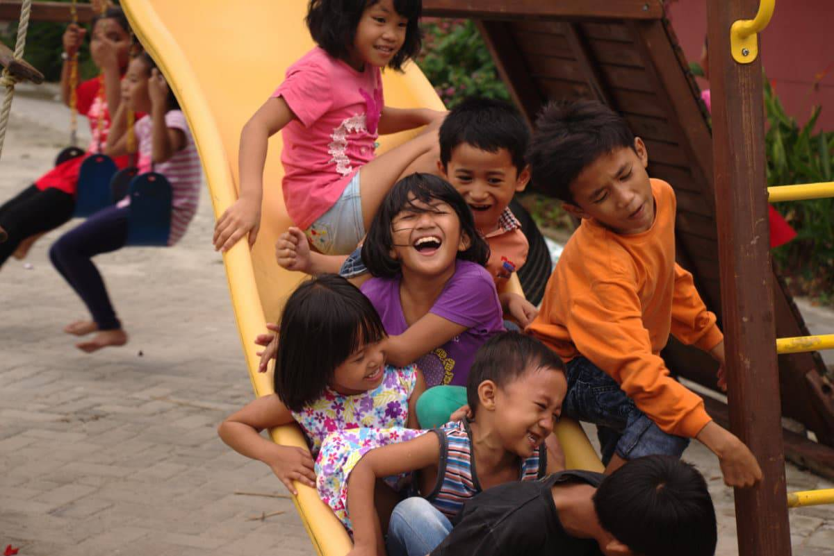 Children from Indonesian orphanage laughing for the camera of ALO7 staff member, Amber.