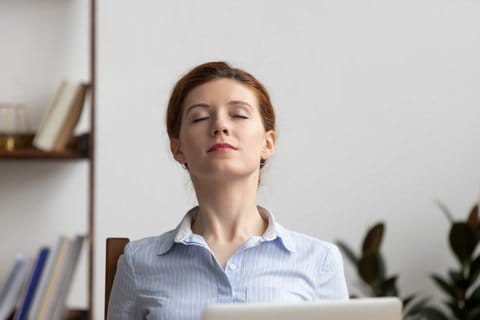 Relaxed Businesswoman Take Deep Breath Of Fresh Air At Workplace