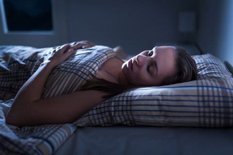 Calm And Peaceful Woman Sleeping In Bed In Dark Bedroom. Lady As