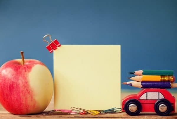 Miniature Red Car Carrying A Colorful Pencils And Red Apple On Wooden Table And Place For Text. Back To School Concept